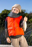 拿着鱼的逗人喜爱的男孩 免版税库存照片