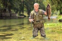 拿着鱼的骄傲的渔夫在河 免版税库存图片