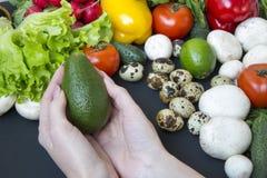 拿着鲕梨的女孩 健康概念的食物 免版税库存图片