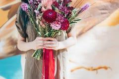 拿着鲜花的花束在光的妇女手 库存图片