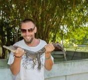 拿着鳄鱼的愉快的微笑的人 免版税库存图片