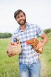 拿着鸡和鸡蛋的愉快的农夫 免版税图库摄影
