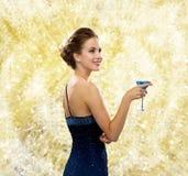 拿着鸡尾酒的晚礼服的微笑的妇女 免版税库存图片