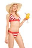 拿着鸡尾酒的红色比基尼泳装的可爱的妇女 免版税库存图片