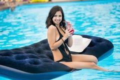 拿着鸡尾酒的黑比基尼泳装的微笑的女孩坐在游泳池的床垫在手段被弄脏的背景  免版税库存照片