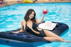 拿着鸡尾酒的黑比基尼泳装的微笑的女性坐在游泳池的床垫在手段被弄脏的背景  库存照片