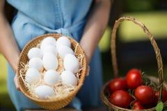 拿着鸡蛋的妇女的中间部分由蕃茄 库存图片