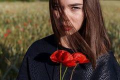 拿着鸦片的美丽的性感的逗人喜爱的女孩在他的手上开花在日落在一个晴朗的夏日 免版税库存图片