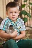 拿着鸭子的逗人喜爱的孩子 库存照片