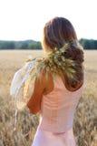 拿着麦子耳朵和帽子在她的手上的桃红色礼服的少妇 库存照片
