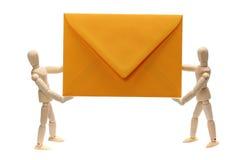拿着黄色信包的二个木玩偶 库存图片