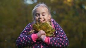拿着黄色叶子的俏丽的女小学生,享受秋天天气,幸福 影视素材