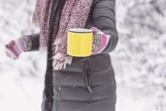 拿着黄色杯子热的饮料的妇女户外 免版税库存照片