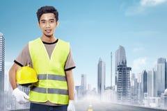 拿着黄色盔甲的可爱的亚裔建筑工人 免版税图库摄影