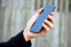 拿着黑智能手机的男性手 图库摄影