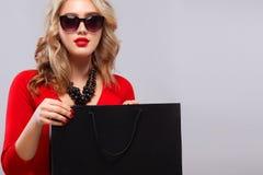 拿着黑暗的袋子的购物的白肤金发的妇女被隔绝在灰色背景黑星期五假日 复制空间待售广告 免版税库存照片