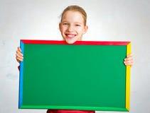 拿着黑板的逗人喜爱的女孩 免版税图库摄影