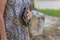 拿着黑钱包的妇女 免版税库存照片