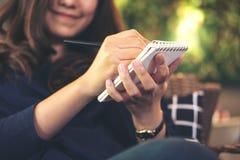 拿着黑铅笔和写在笔记本的一名美丽的亚裔妇女坐在与迷离绿色垂直庭院的现代咖啡馆 免版税库存照片