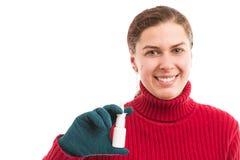 拿着鼻孔喷射的微笑的妇女 免版税库存照片