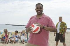 拿着齐射球的人在与朋友的海滩被编组后边 免版税图库摄影