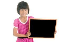 拿着黑人委员会的小亚裔女孩 免版税库存照片