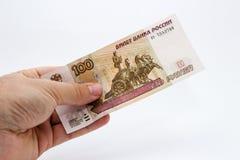拿着100俄罗斯卢布笔记的一只白种人男性手的照片的关闭 库存照片
