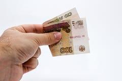 拿着100俄罗斯卢布笔记的一只白种人男性手的照片的关闭 库存图片