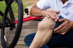 拿着他受伤的膝盖的下落的骑自行车者的中间部分 免版税库存照片