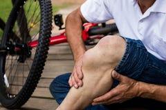 拿着他受伤的膝盖的下落的骑自行车者的中间部分 免版税库存图片
