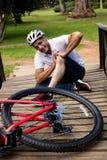 拿着他受伤的膝盖的下落的骑自行车者 图库摄影