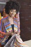 拿着织品的一位非裔美国人的女性裁缝的画象 图库摄影