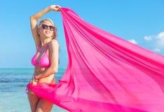 拿着织品的片断在风的桃红色比基尼泳装的少妇 图库摄影