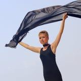 拿着黑织品的黑晚礼服的美丽的少妇在风在海边 免版税图库摄影