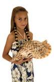 拿着贝壳的可爱的棕褐色的女孩穿海岛样式礼服 免版税库存照片