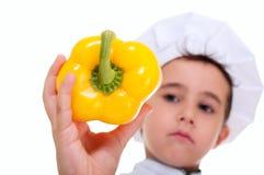 拿着水多的黄色辣椒粉的小男孩院长 免版税库存图片
