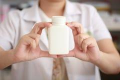 拿着医学瓶的药剂师手 免版税库存照片
