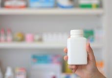 拿着医学瓶的药剂师手 免版税库存图片