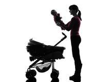 拿着婴孩剪影的妇女摇篮车 库存照片