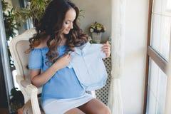 拿着婴孩衬衣的孕妇 图库摄影