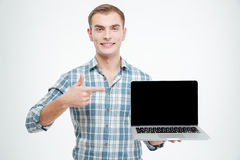 拿着黑屏膝上型计算机和指向对此的微笑的人 库存照片