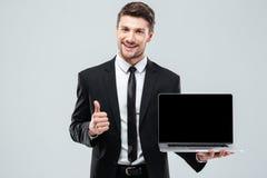 拿着黑屏膝上型计算机和显示赞许的快乐的商人 库存图片