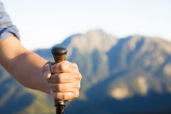 拿着登山杖和山背景的手 库存图片