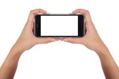 拿着水平的巧妙的电话,用途裁减路线的女性手 免版税库存照片
