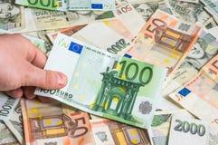 拿着100张欧洲钞票的手 免版税库存图片