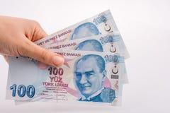 拿着100张Turksh里拉钞票的手手中 库存照片