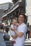拿着他愉快的小儿子,户外北京的微笑的父亲画象 免版税库存图片