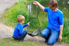 拿着他们抓的鱼的父亲和儿子 免版税图库摄影
