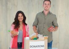 拿着从捐赠箱子的微笑的夫妇eatables 库存照片