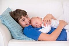 拿着他新出生的小兄弟的男孩 库存照片